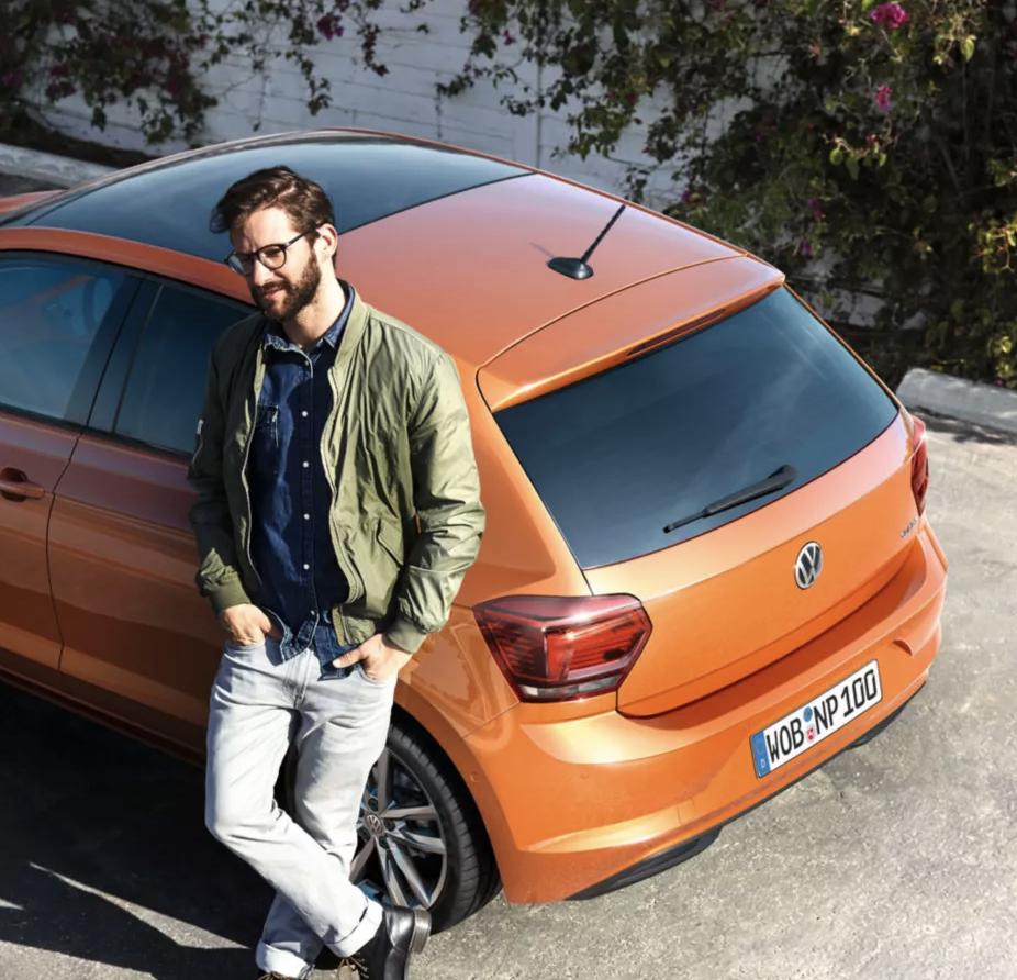 hombre con su nuevo volkswagen polo naranja metalizado