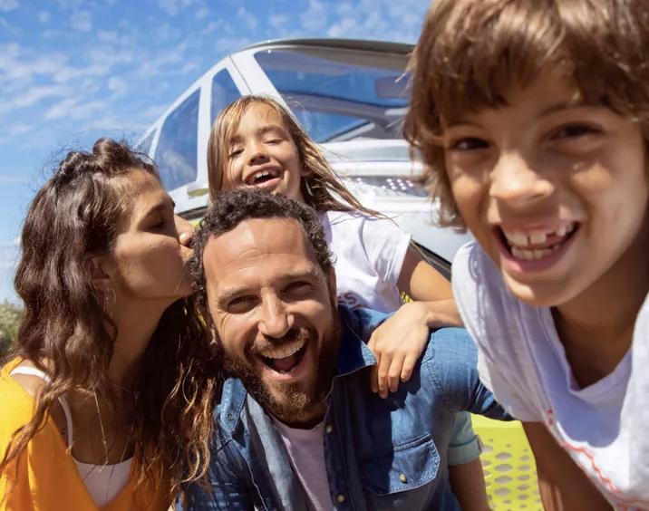Familia delante de su coche familiar blanco posando para una foto
