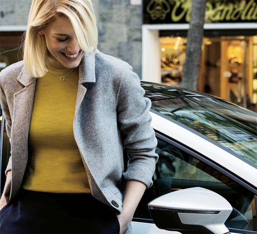 mujer apoyada en uno de los modelos de coches seat